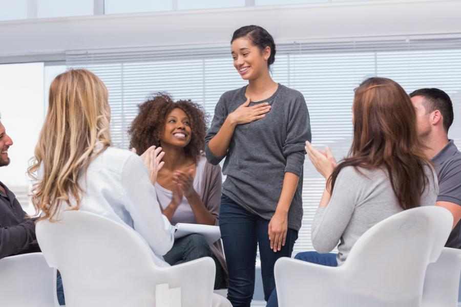 woman standing in center of group therapy meeting